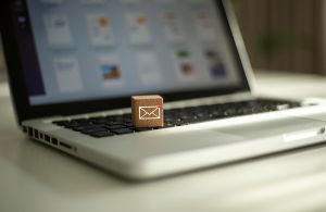 Wooden box with email logo sitting on laptop.