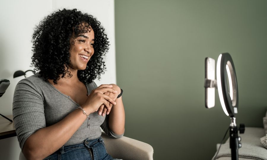 Woman sitting down and filming a video in front of a light and phone setup.